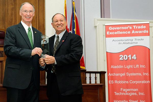 PESA a reçu le Prix de l'Excellence commerciale à l'occasion de la 8ème cérémonie du même nom organisée par le gouverneur républicain de l'Alabama, Robert Bentley (à gauche) le 5 mars 2014 en présence de Chuck Tillett (à dr.), président jusqu'en novembre dernier de PESA.